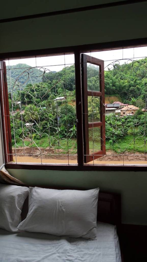The interior of a room in a budget guesthouse in Laos with a bed next to a window with a grille overlooking a mud bank of a river