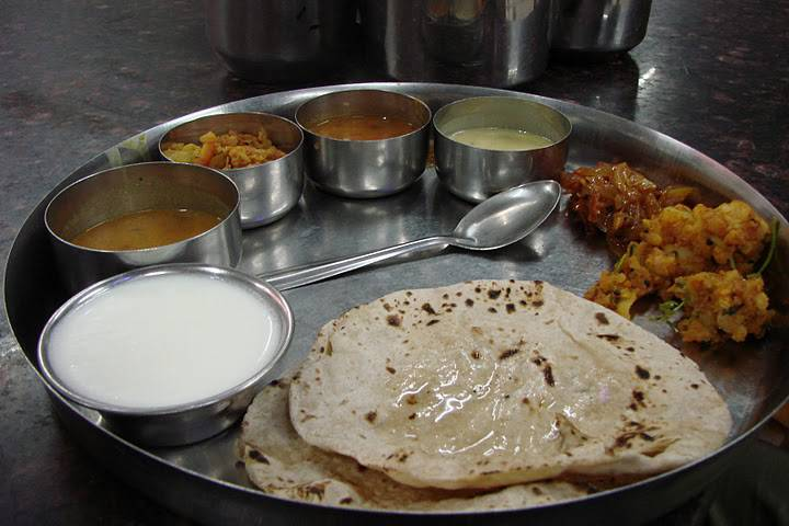 Indian thali (selection of dishes on a steel plate) including flat breads called chapatis and a few bowls with vegetable dishes and yoghurt.