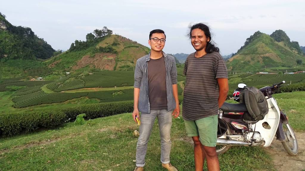 Sayak with his new Vietnamese friend and a motorbike, the hilly landscape of tea gardens in Moc Chau behind them.