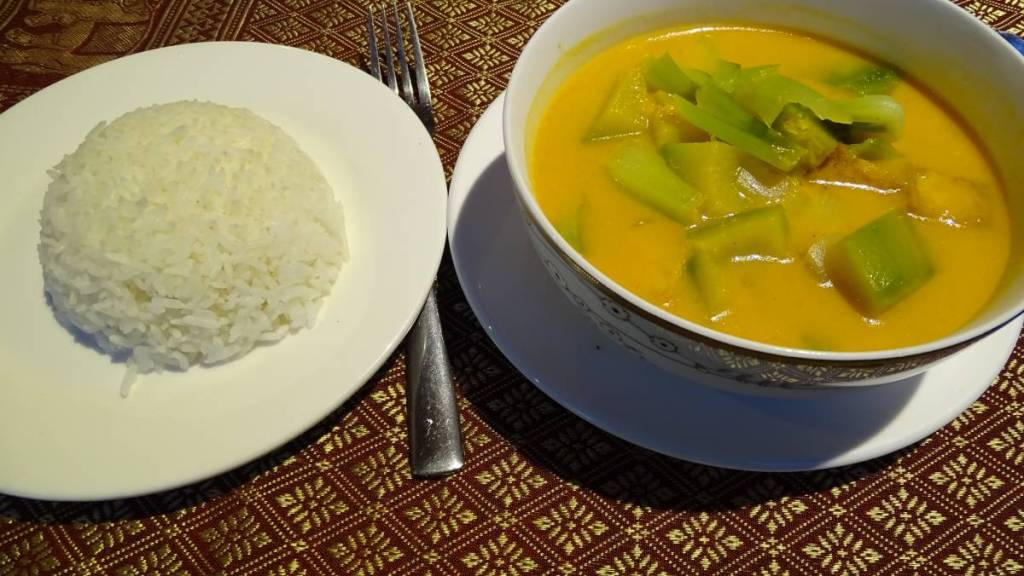 A bowl of khmer vegan pumpkin curry and an accompanying plate of white rice
