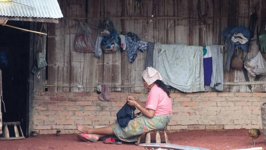 Laotian woman sewing clothes on a low stool in front of her wooden hut.