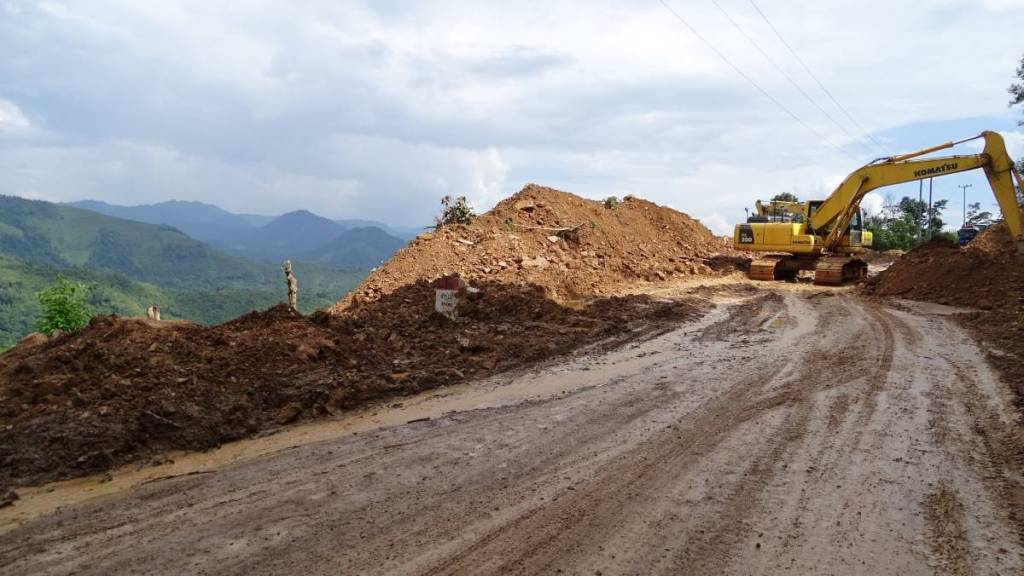 An electric digger clearing the landslide on the muddy road in the mountains in Laos