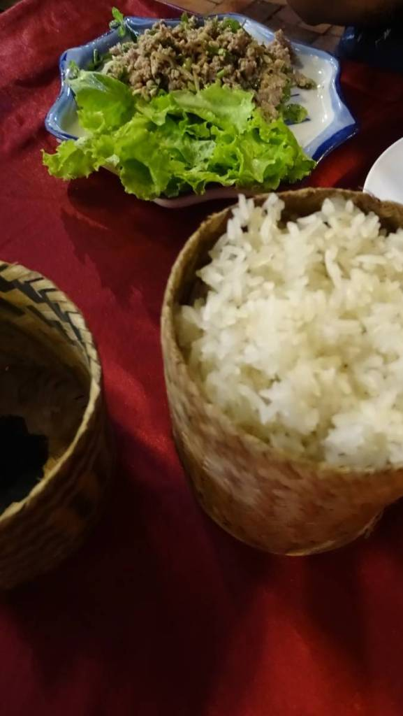Sticky rice served in a small bamboo basket and a plate of minced tofu larb- typical Laotian food in vegan version