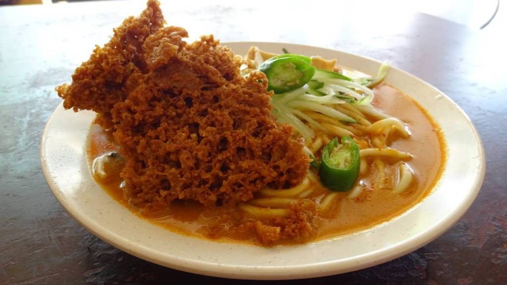 Nyonya dish from Malaccan vegan restaurant: a plate brimmed with noodles in a thick  sauce and topped with a deep fried crunchy batter