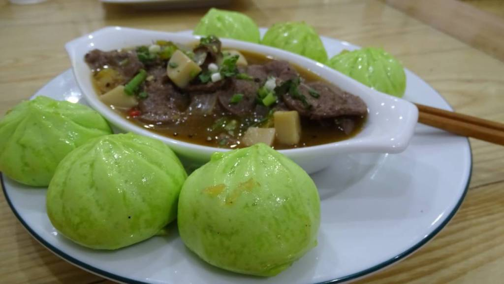 Tiny green steamed buns accompanying mock meat slices in gravy