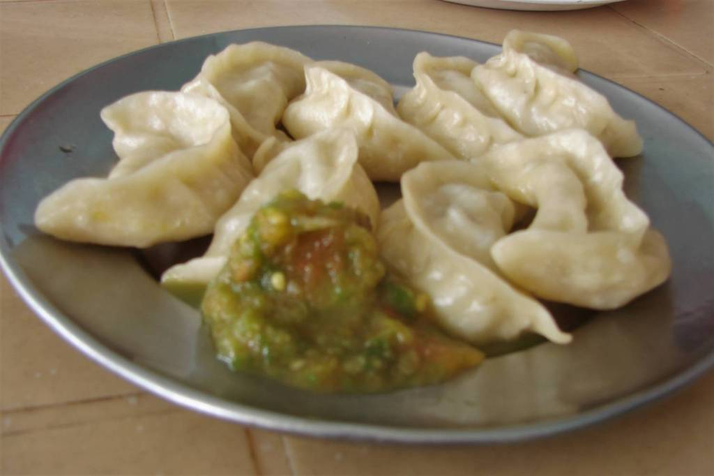 A steel plate full of momos- Indian dumplings .