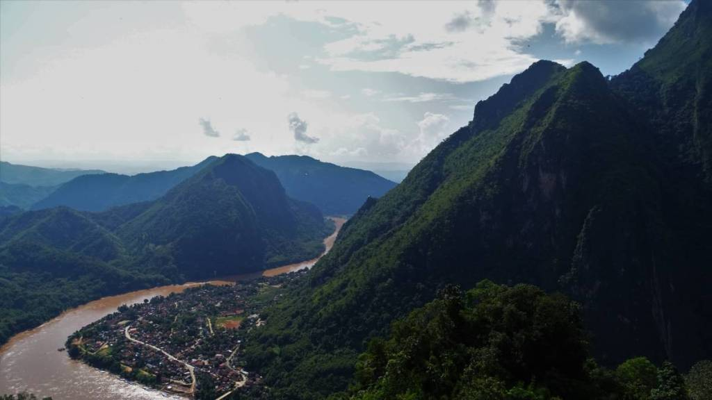A view from above at a large, brown-colour river and a tiny town hugging the foot of steep forest- covered mountains.