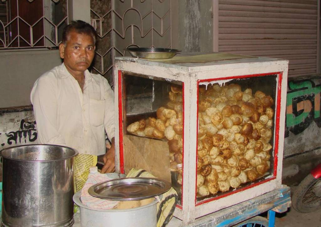 A pani puri/ fuchka seller at his street stall at night.