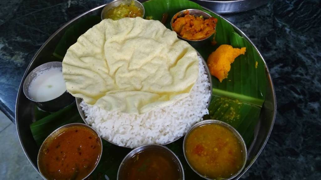 South Indian thali: meal on a steel plate, containing rice, crispy poppadam wafer and a selection of small bowls with vegetarian saucy dishes