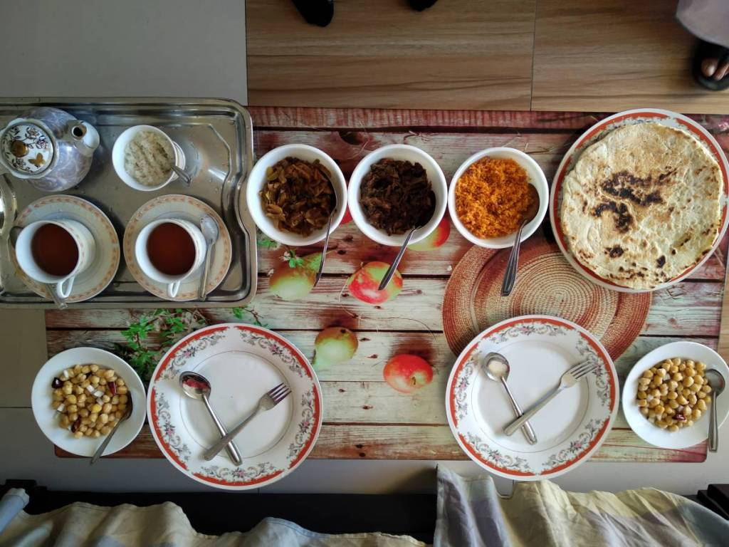 An aesthetically set breakfast table in Sri Lanka with flat bread rotis, chickpeas, coconut sambal and other dishes and a tray with tea.