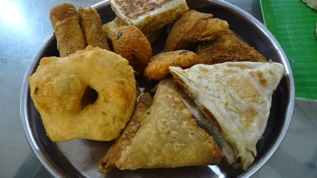 A steel plate full of Sri Lankan fried snacks such as doughnut vadas and deep fried pastries.