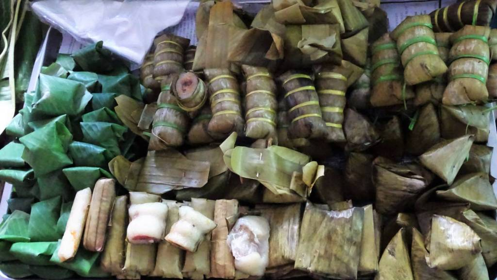 A selection of sticky rice swets wrapped in banana leaves and tied with strings from the market in Cambodia