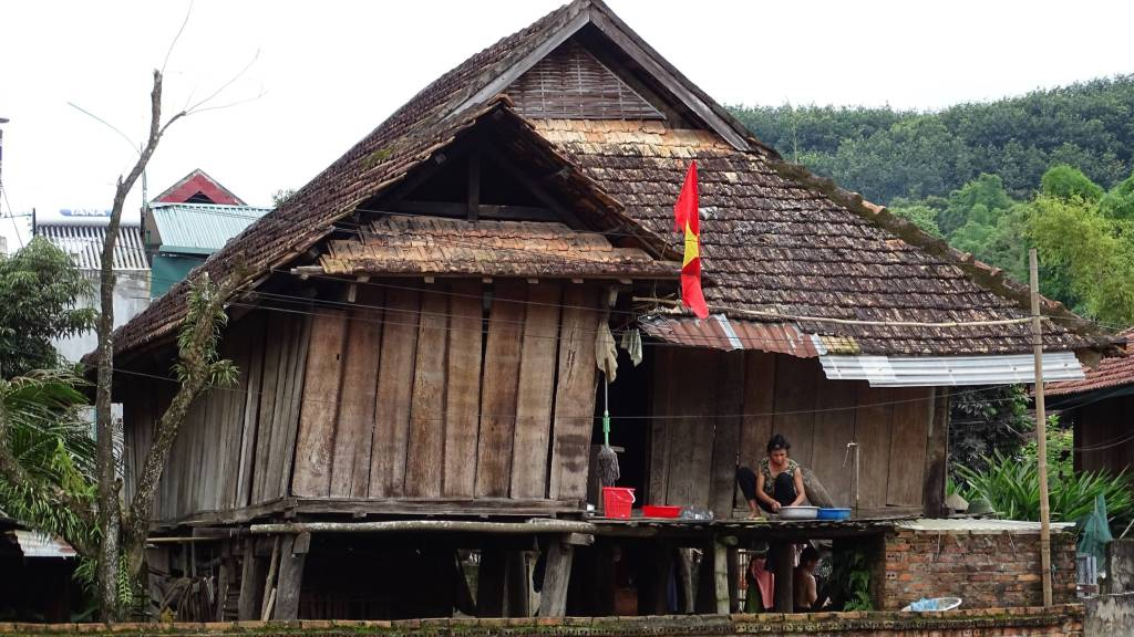A Tai minority woman doing the laundry on the veranda of her wooden, stilted house in Ban Man village near Dien Bien Phu