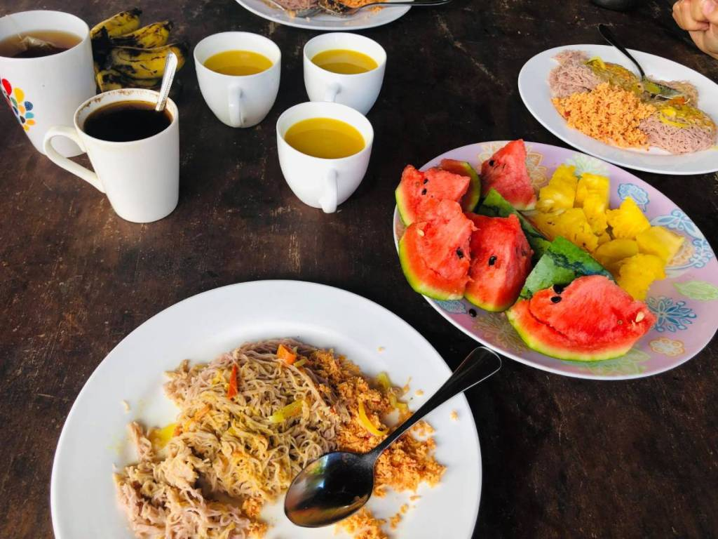 Breakfast table in Sri Lanka: plates with noodle-like string hoppers and coconut sambal, a platter with watermelon and fruit juice