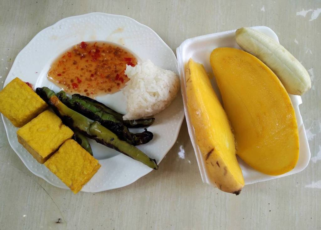 Self-made vegan breakfast from Thai market: a small lump of sticky rice with sweet-sour sauce, grilled green peppers, fried tofu cubes plus two slices of mango and a small banana