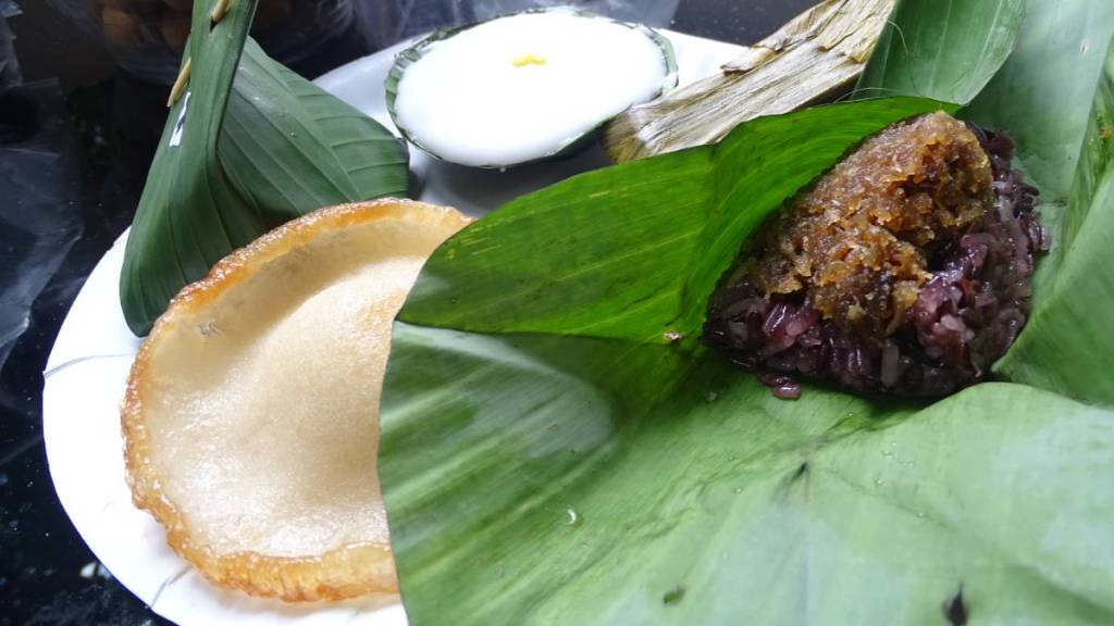 Selection of Thai sweets, some wrapped in leaves: sticky red rice with coconut topping, coconut pancake, steamed cupcake