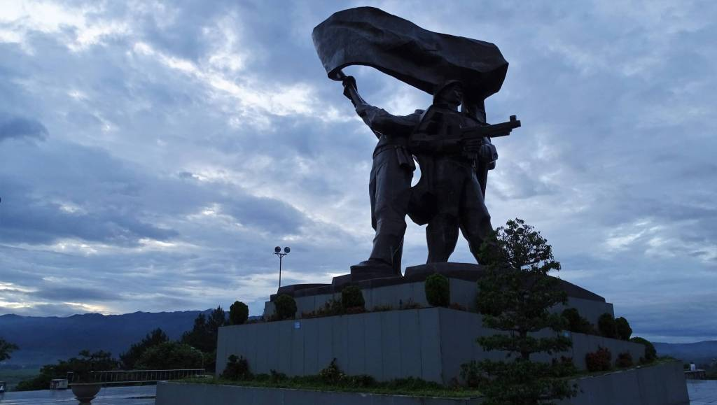 The Victory Monument in Dien Bien Phu: a large statue of three figures standing back to back, placed on the top of a large hill, with mountain range in the background