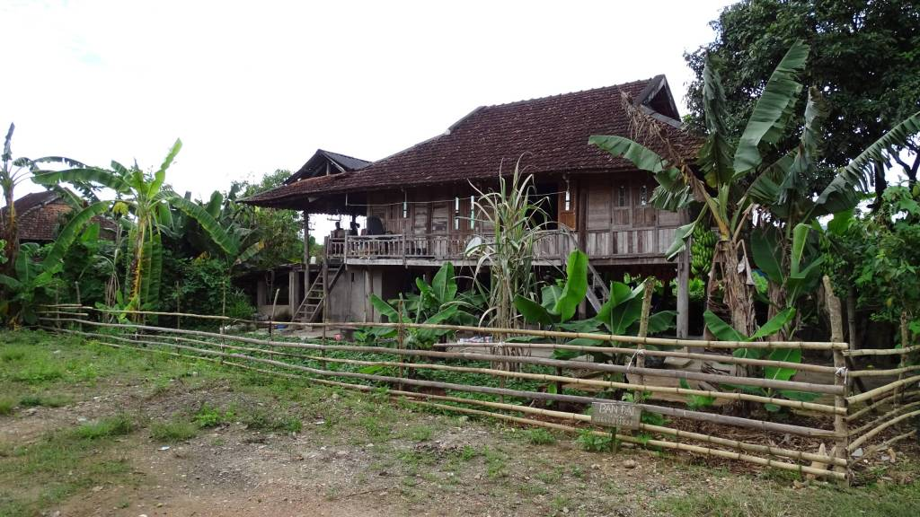 Traditional wooden stilted house near Dien Bien Phu, surrounded with a bamboo fence and a small garden