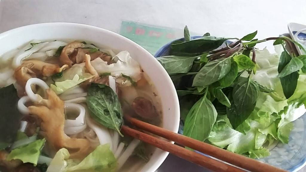 A bowl of vegan pho- Vietnamese noodle soup- with mushrooms and mock meat and a huge bunch of herbs on a plate next to eat