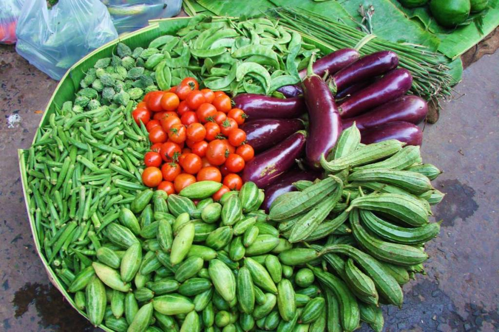 A basket at the Indian market, full of various green vegetables, aubergines and tomatoes