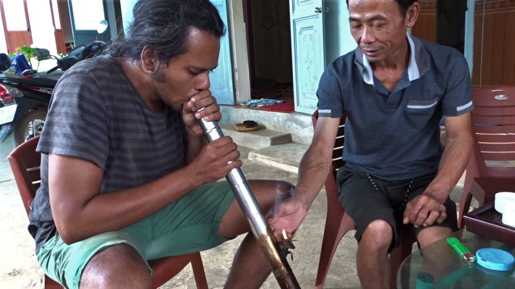 Sayak taking a puff of an enormous, steel Vietnamese pipe and a Vietnamese man helping him to keep the pipe burning