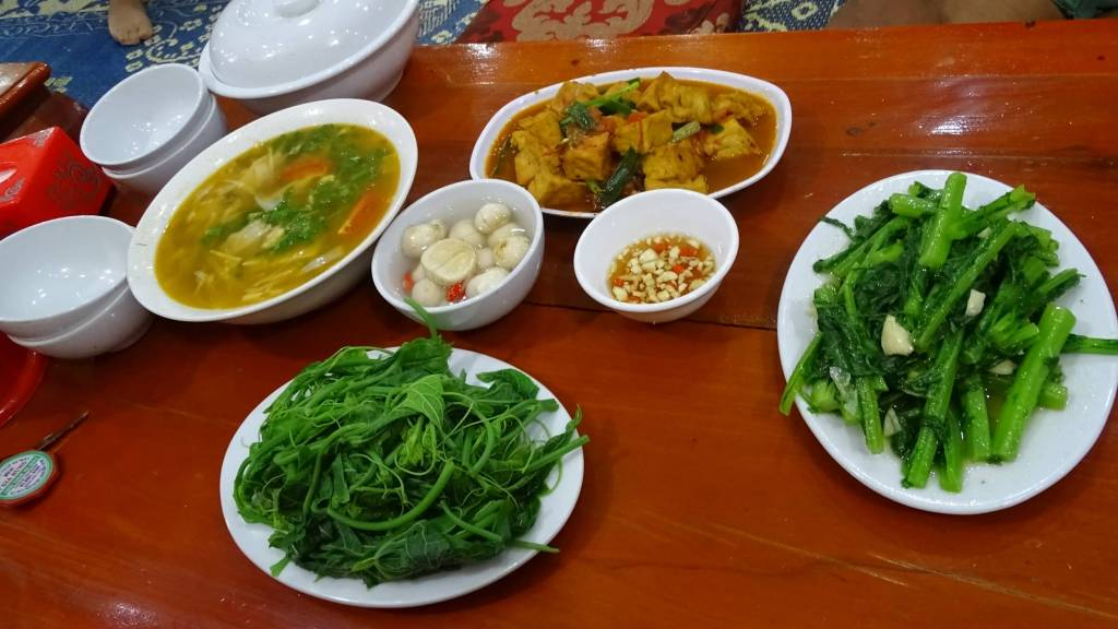 A selection of Vietnamese vegan dishes including tofu, pickles and boiled greens.