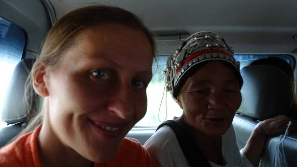 The author sitting in a minivan with an elderly lady from Akha tribe, wearing characteristic headdress decorated with silver coins