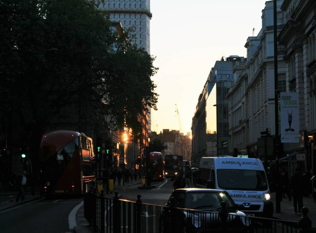 A street in London city centre with some buses and cars, barely visible in the coming dusk