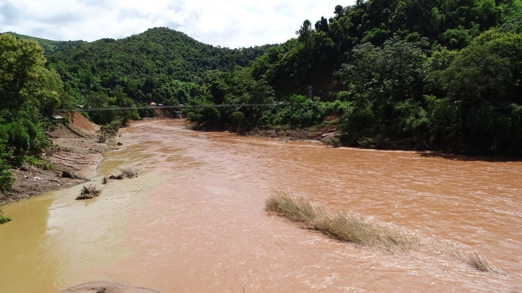 The view at Nam Phak river, brown and swollen in the rain season and the forested banks, taken in Pak Nam Noi.