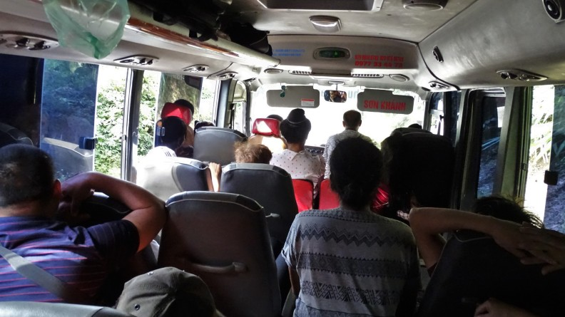 An overcrowded interior of a bus in Laos with seats in the aisle