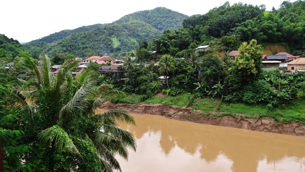 Tributary of Nam Ou, swollen, brown from sediments, flows through a small Muang Khua village set in lush greenery of north-east Laos.