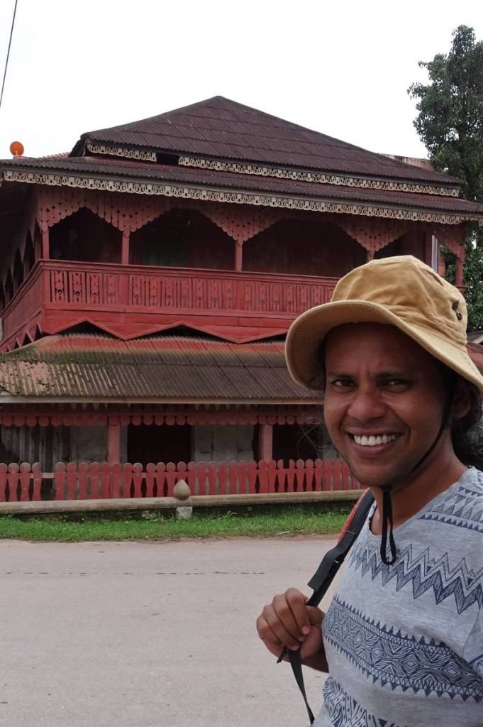Sayak in front of the tourist information centre in Muang Sing - a 2-storied, red, wooden building with intricately decorated balcony