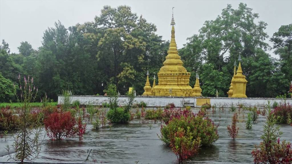 Yellow painted stupa among the greenery