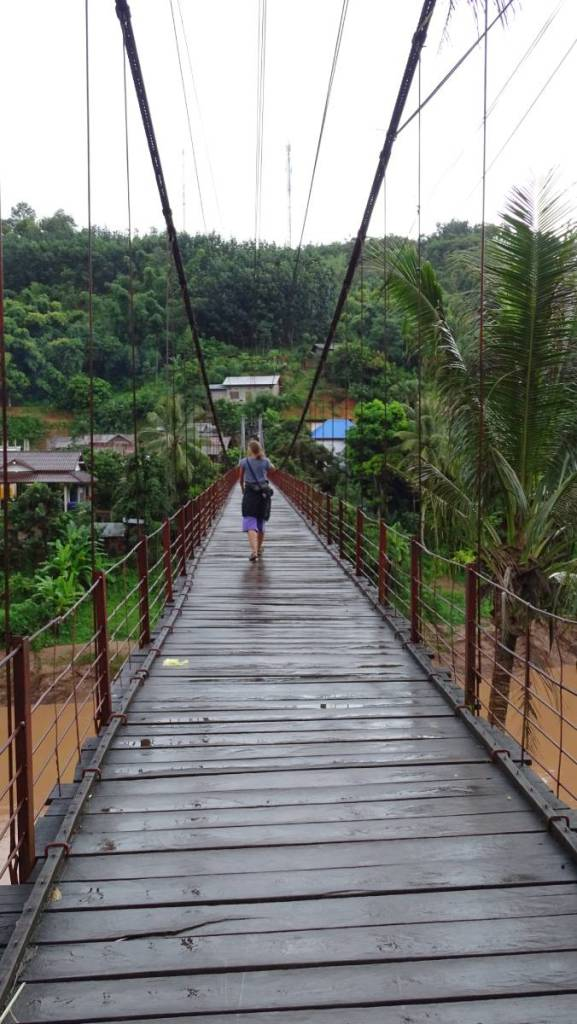 Author walking down a suspension bridge over a dark brown river, connecting two parts of Muang Khua village