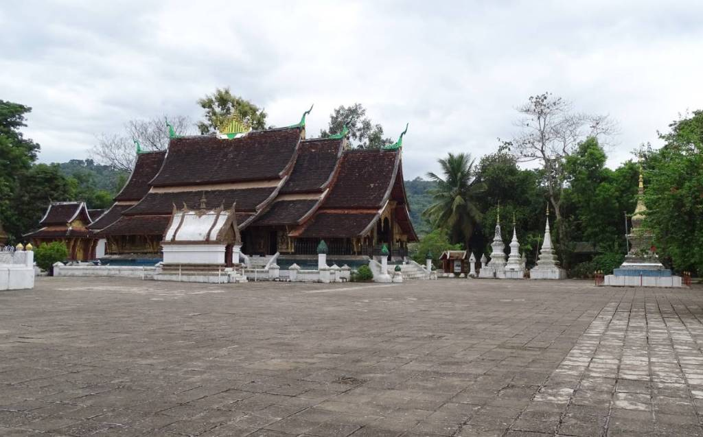 A characteristic cascading multitiered roof of the Wat May in Luang Prabang dominates the temple courtyard