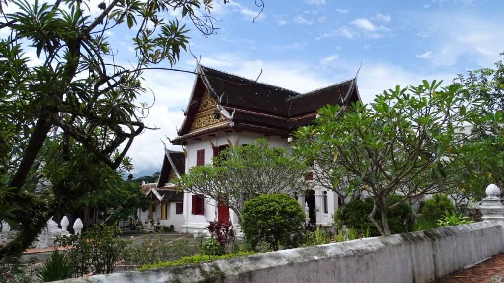 A whitewashed Wat Souvana Khiri with a Laotian roof bearing colonial architecture traits stands behind a white stone wall among small trees and plants
