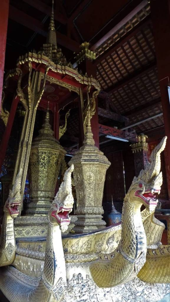 A golden boat decorated with multiple snake or dragon heads  with two huge golden urns under a canopy stands inside one of the temple buildings in Luang Prabang