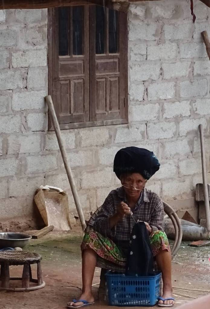 An old Yao woman sitting in front of her house on a small stool looks from above her stitching at the camera