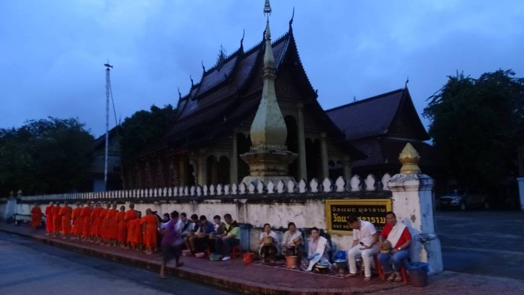 A row of loca men and women sitting on low stools wait for the approaching line of monks in orange robes in the early hours of the morning during the alms giving ceremony in front of an old wat in Luang Prabang
