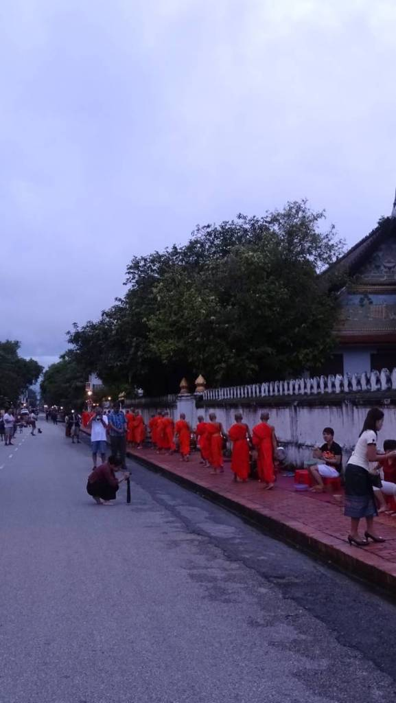 The main street in Luang Prabang at down is full of tourists taking photos of a line of monks novices walking clean shaven, b arefoot with their begging bowls across their shoudlers