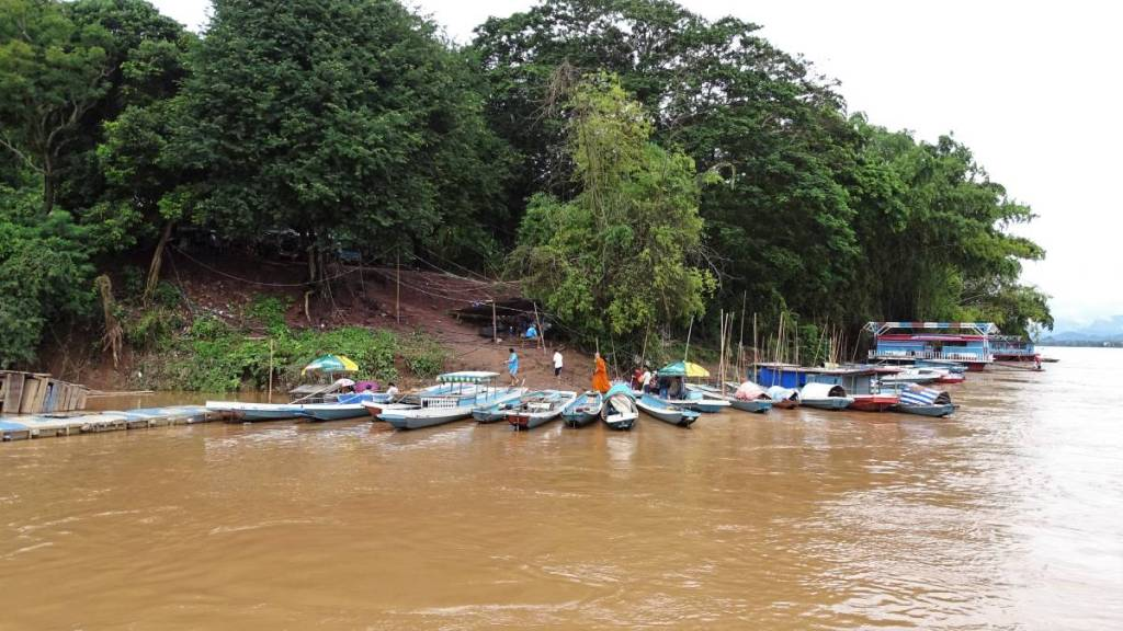 A steep, muddy boat landing on the Mekong in Xieng Men village in Laos. Lots of tiny, narrow boats are moored to the bank in semi-circle and a few children walk up the path to the village.