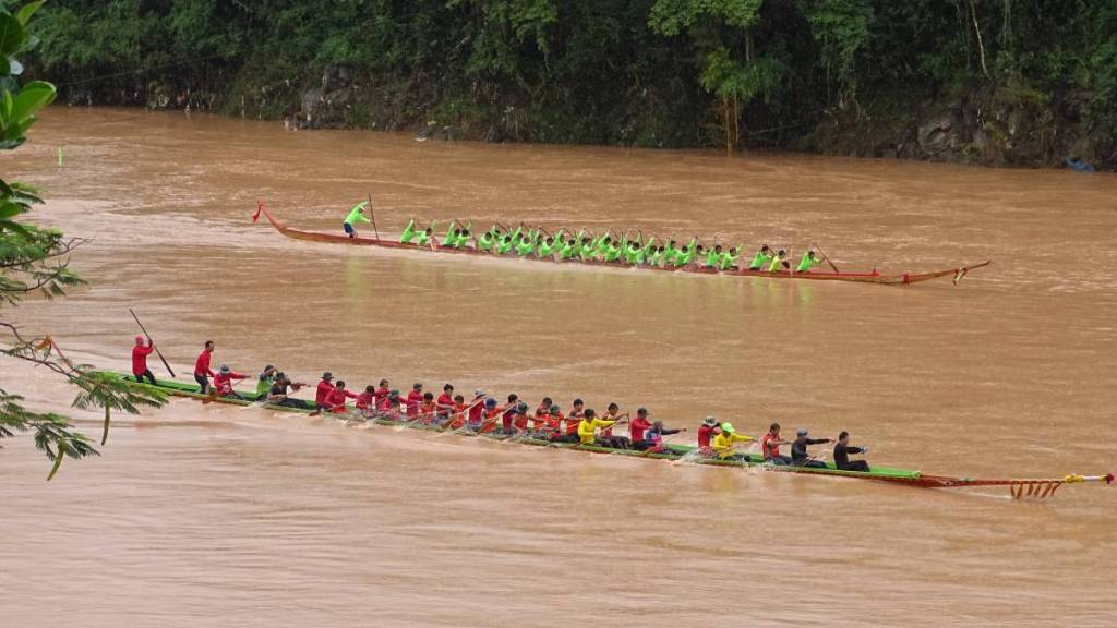 Two competing teams of rowers in their long, narrow boats race on Nam Khan river in Laos.