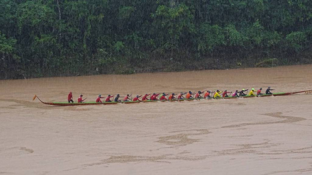 A long narrow boat with 20 rowers of board is moving at the full speed in the pouring rain during boat racing festival in Laos.
