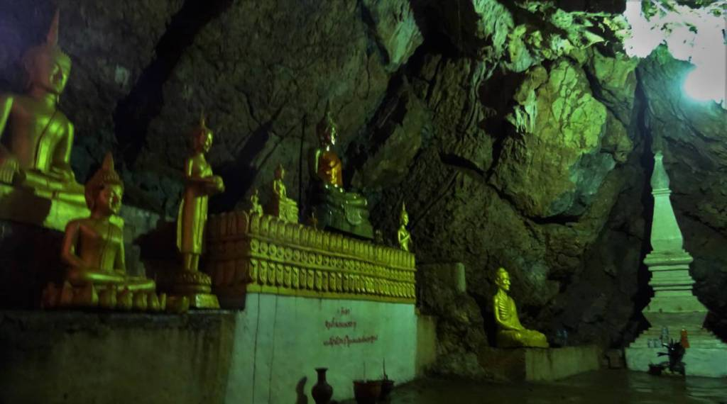Dozens of small, golden, seated and standing Buddha statues inside a cave at Wat Tham Sackkalin in Laos