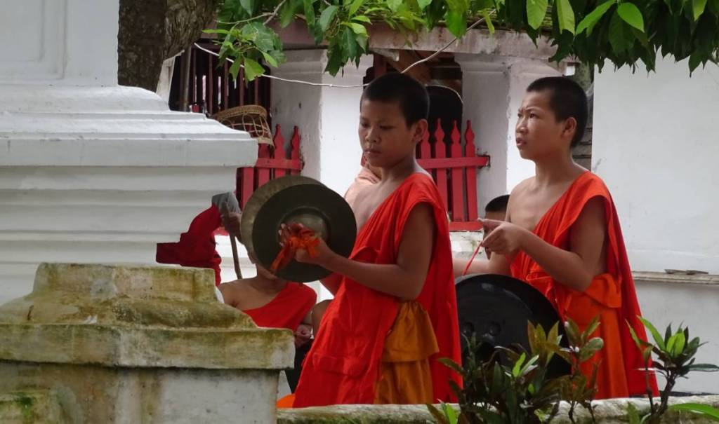 Buddhist monk novices in orange robes playing on gongs in front of a wat
