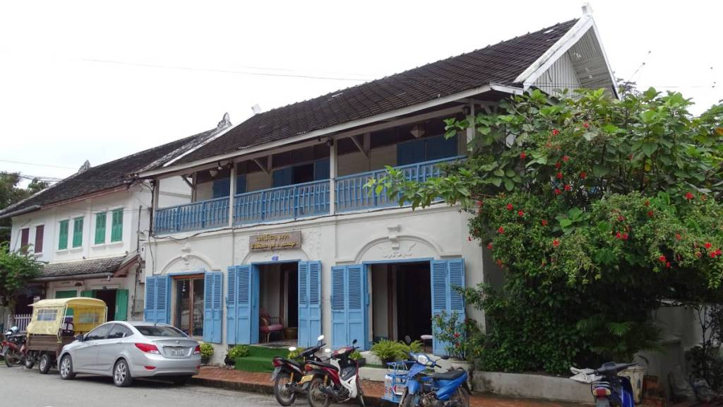 Large, whitewashed colonial style building with a roofed balcony and blue wooden shutters located on the main road in old Luang Prabang