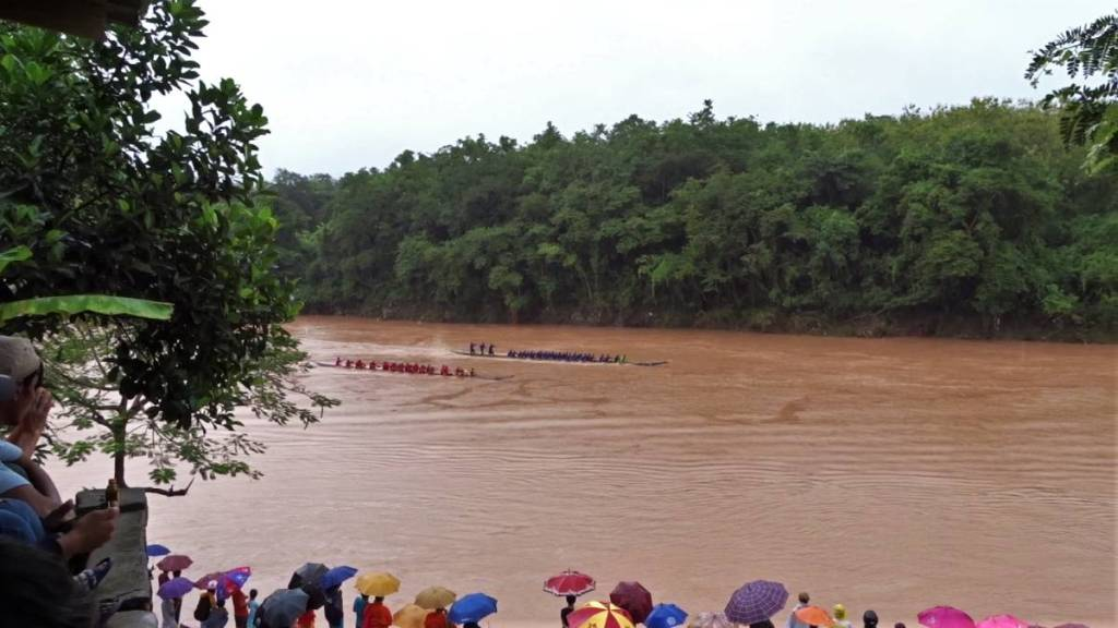 A crowd of villagers, many holding the umbrellas are watching the boat race held on a brown-coloured river in Laos