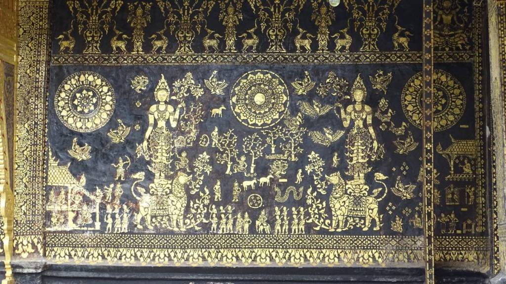 Gilded golden decorations on a black wall in a wat in Luang Prabang, presenting female figures riding lions and plenty of smaller figures surrounding them