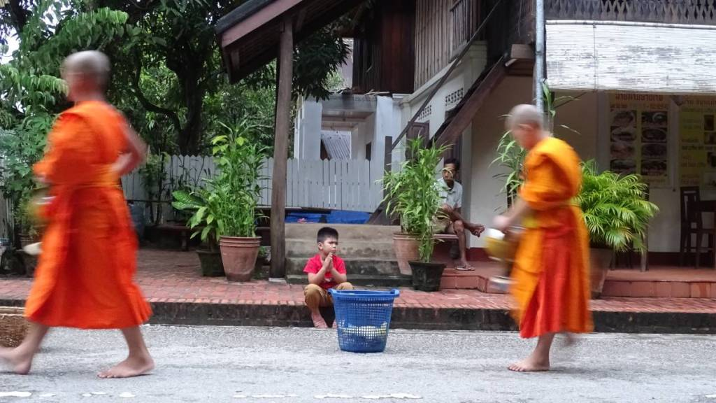 A small boy with hands held like in prayer sits on a curb in front of his house with a large baskets, waiting for the passing monk novices- clean shaven and barefoot boys- to throw some treats they got during the alms giving ceremony