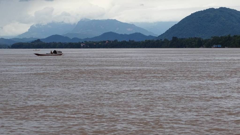 Wide Mekong, a single traditional boat and outlines of mountains  half-covered in clouds in the background